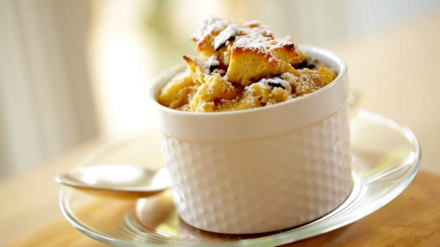 Single serving of a mini Banana Bread Pufdding served in a white ramekin