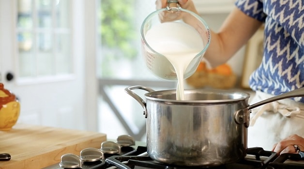Pouring milk and cream mixture into large pot on stove