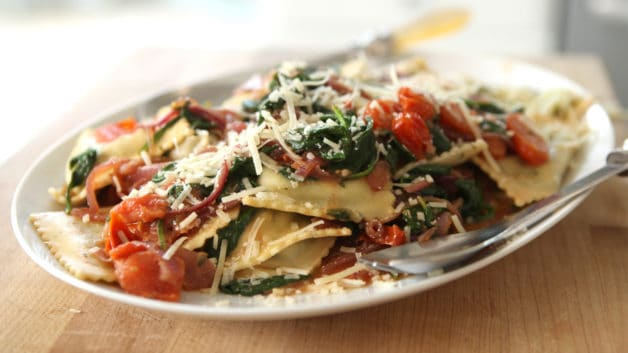 Spinach Ravioli with Spinach, Tomatoes and Caramelized Onions on a white platter