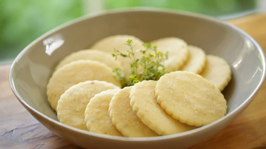 Lemon Thyme Sugar Cookies arrange in an escargot pattern in a gray bowl with a sprig of Thyme