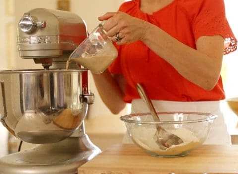 A person pouring earl gray mixture into a stand mixer