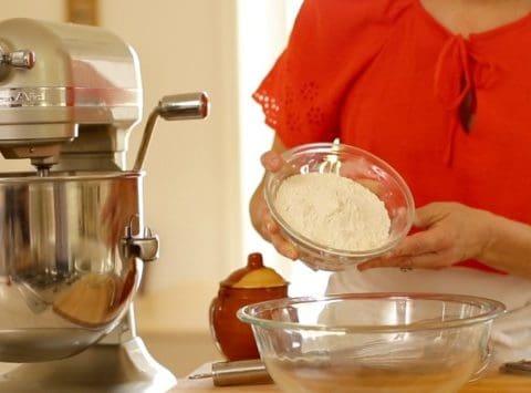 a person adding flour to bowl