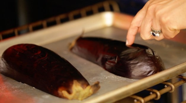 a person checking eggplant for doneness in the oven
