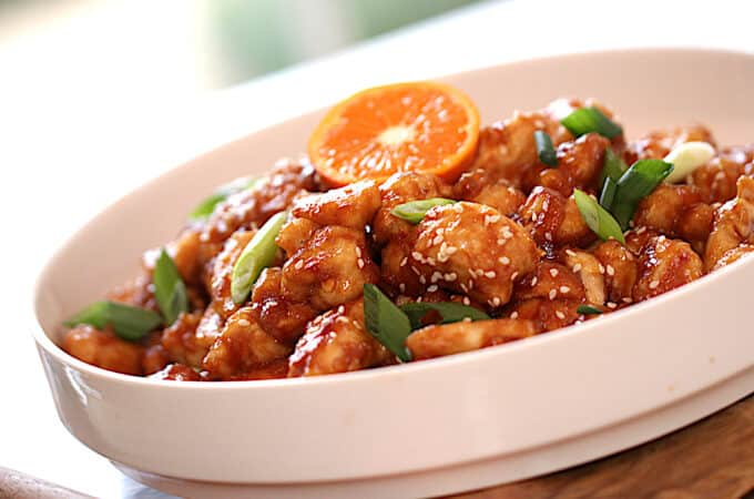a finished plate of orange chicken garnished with green onions and a slice of orange