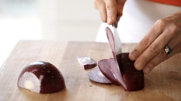 slicing red onion into half moons