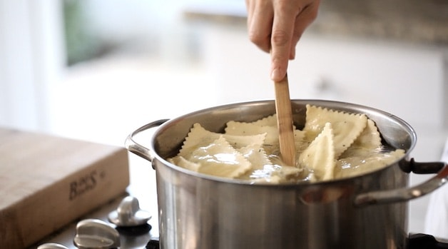 cooking spinach ravioli in a pot and stiring with spoon