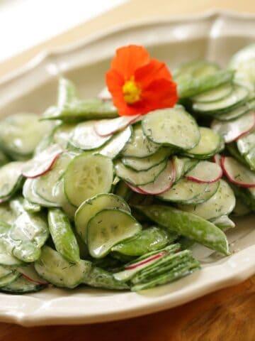Cucumber Salad on a white Platter with Nasturtium