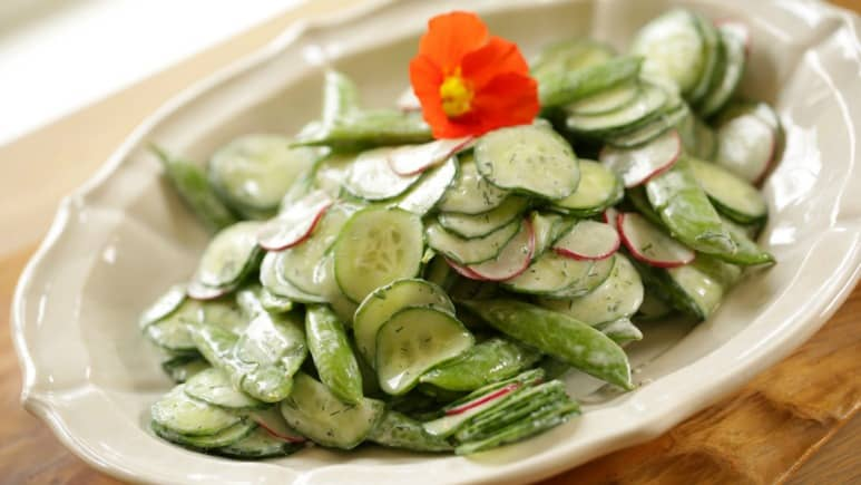 Creamy Cucumber Dill Salad on a plate with nasturtium