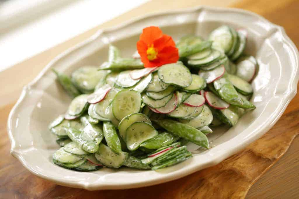 Creamy Cucumber Dill Salad Recipe topped with a nasturtium flower garnish