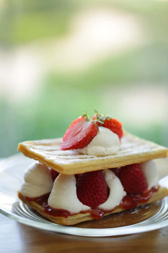 2-layer strawberry napoleon on a glass plate filled with whipped cream