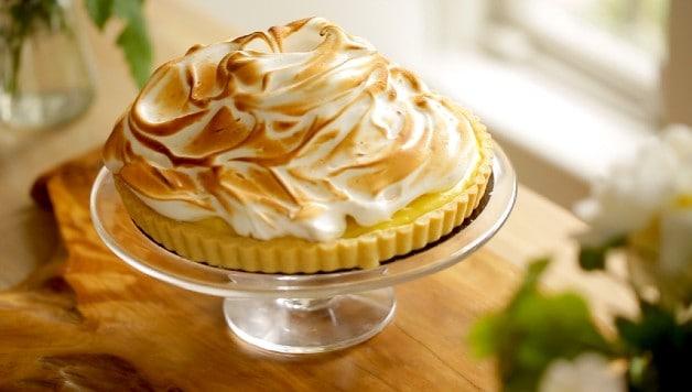 Lemon Meringue Tart on cake stand resting on wooden board