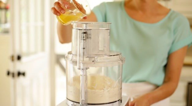 Beaten egg mixture being poured into a food processor