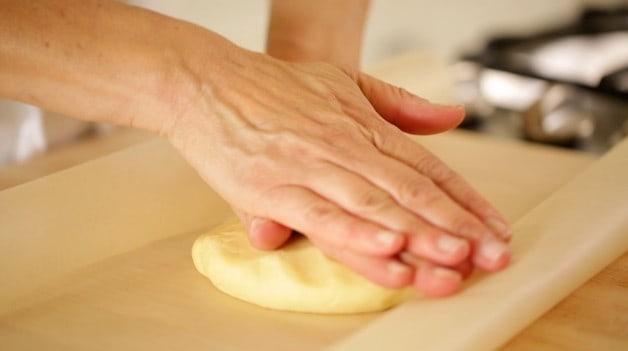 Two hands pressing dough ball into a disk for tart dough