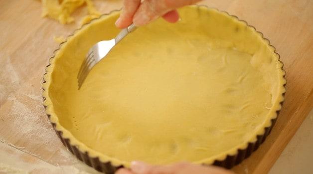 fork pricking dough in tart dish