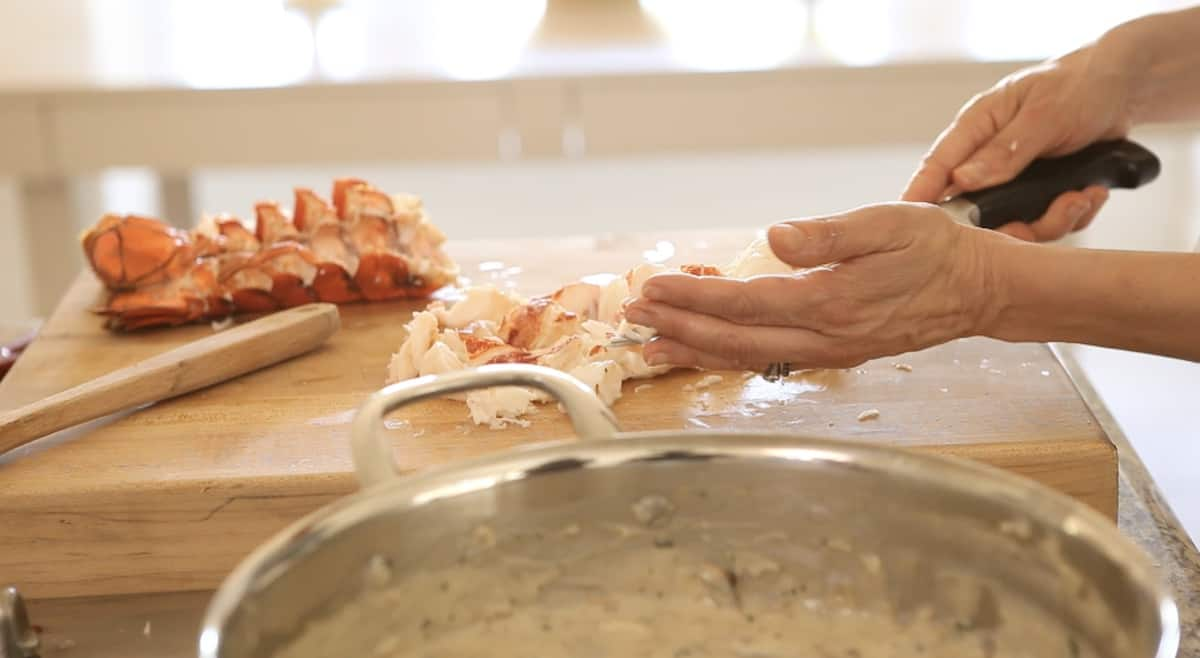 adding cooked lobster pieces into a skillet with lobster thermidor sauce