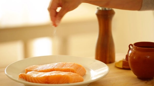 Salmon fillets being seasoned on a white plate
