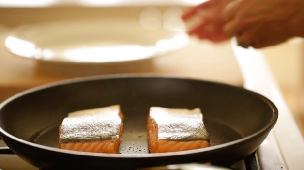 Salmon searing in a pan skin side up