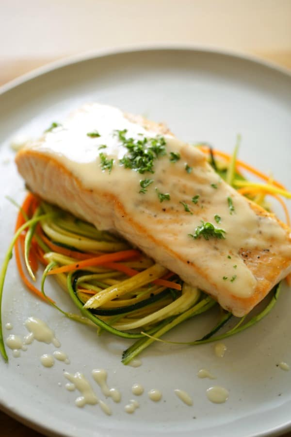 Vertical Image of Seared Salmon with a French-Style Buerre Blanc Sauce and Thinly Sliced Vegetable Nests