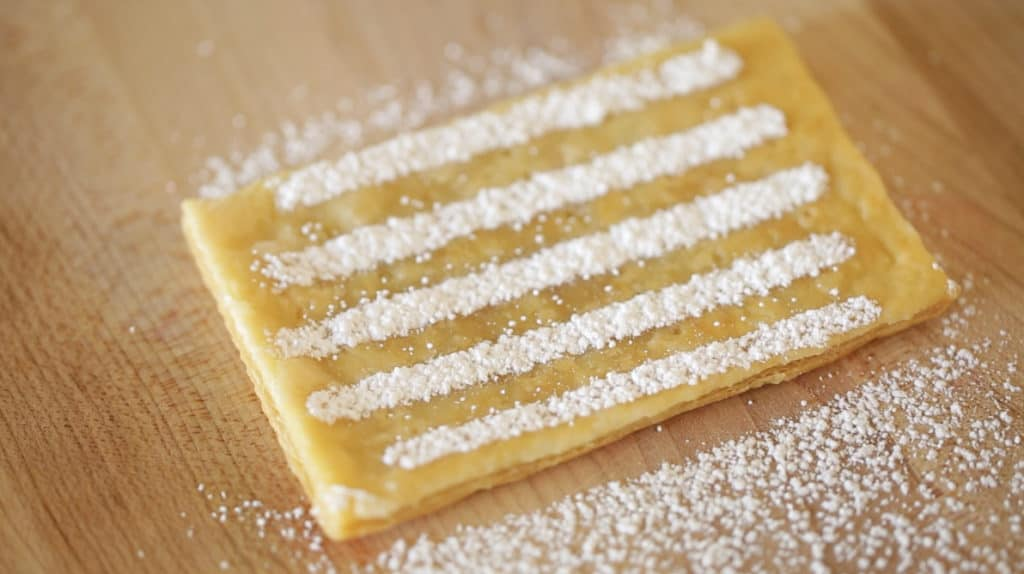 Powdered Sugar stripe on a puff pastry rectangle for a Strawberry Napoleon