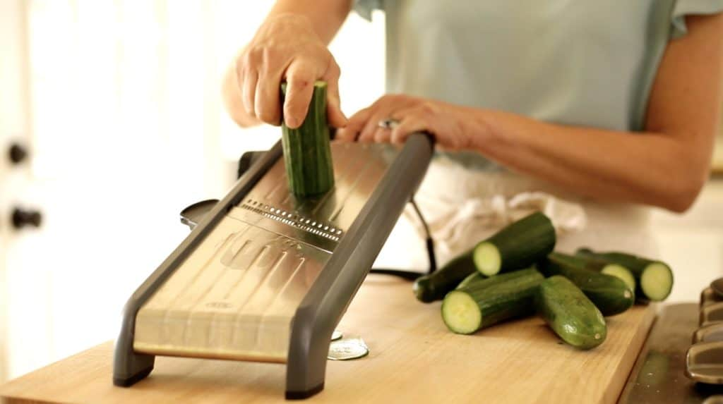 English cucumbers being sliced in a mandoline for Creamy Cucumber Dill Salad Recipe