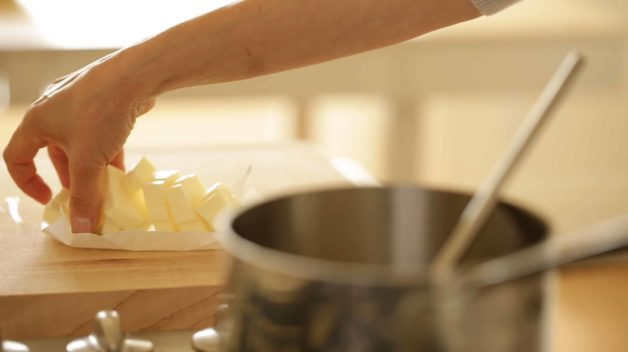 Adding butter cubes to a sauce pot