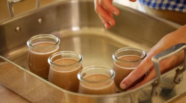 A person adding pudding pots into a roasting pan