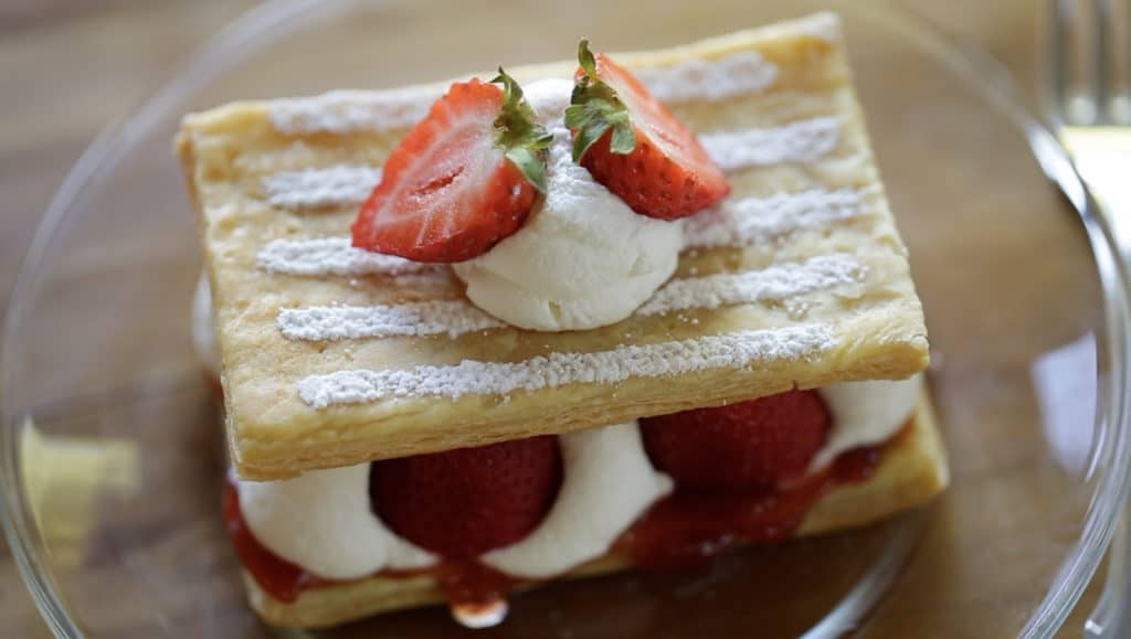 Overhead view of a strawberry Napoleon on a plate with a powdered sugar stripe