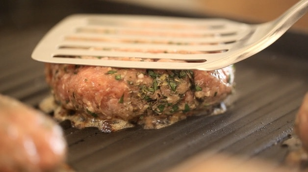 Flattening a burger on a grill with a spatula