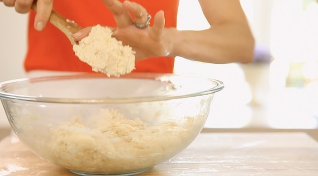 Scrapping dough off a wooden spoon into a clear bowl