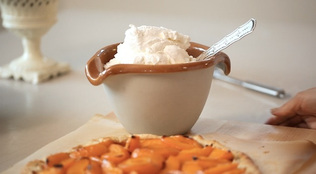 Bowl of whipped cream beside an Apricot Galette