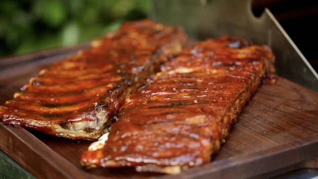 2 racks of BBQ Ribs with BBQ Sauce on cutting Board