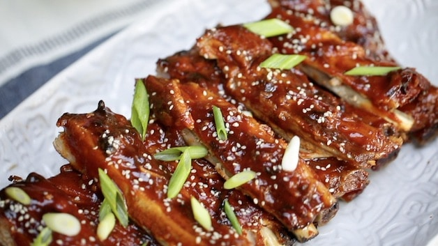 BBQ Ribs garnished with green onions and sesame seeds on white platter
