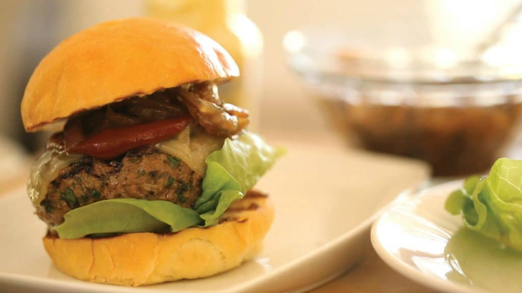 an ultimate burger recipe being served on a white plate with a white plate with bibb lettuce to the side and a bowl in the background