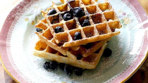 a stack of blueberry waffles stacked on a plate and dusted with powder sugar and topped with berries
