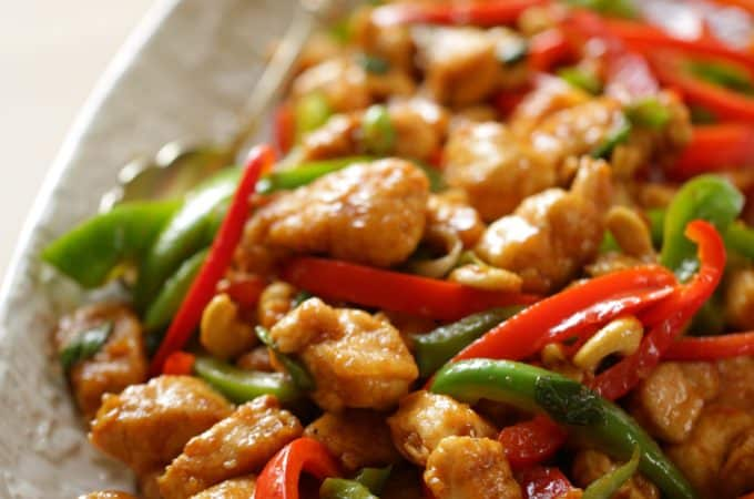Easy Cashew Chicken Recipe in an oval platter vertical orientation