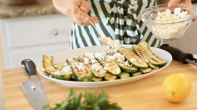 adding goat crumbled goat cheese to a platter of grilled zucchini