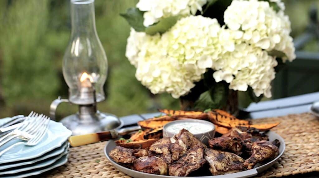 Grilled chicken and sweet potatoes on a table outside with flowers
