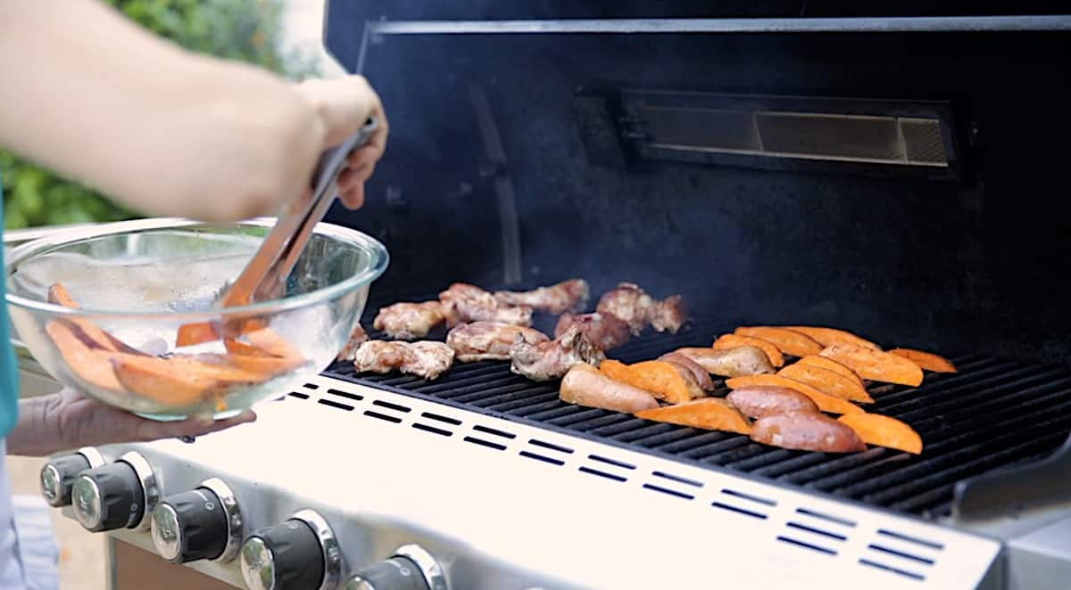 adding sweet potatoes to a grill with chicken