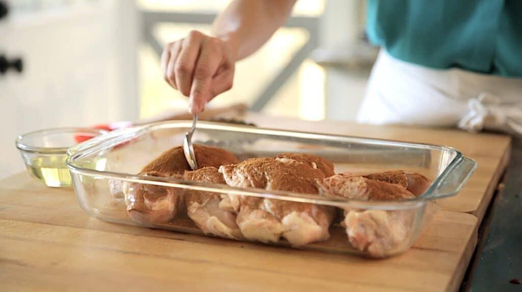 adding cinnamon rub to raw chicken in a casserole dish