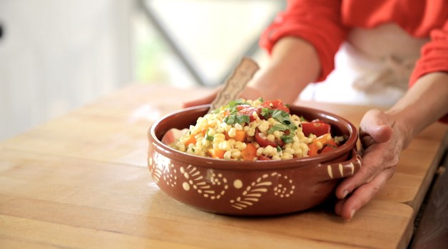 A corn Salad in a Terra Cotta Bowl on a cutting board