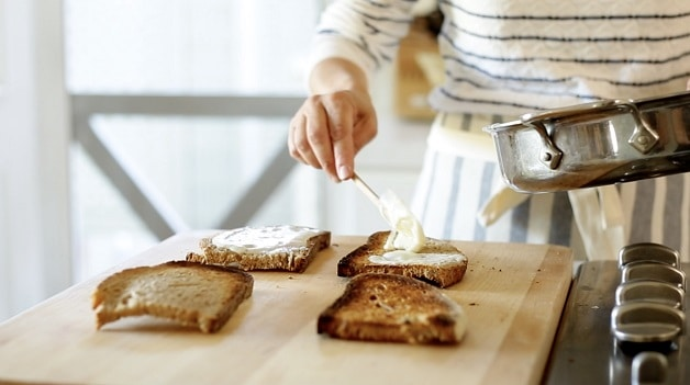 Spreading bechamel sauce over sandwich bread