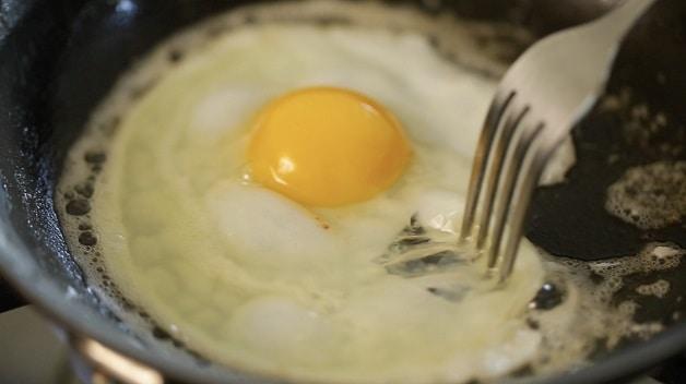 Fork shifting egg inside of pan