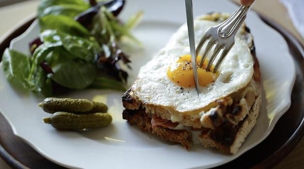 Slicing into Croque Madame sandwich