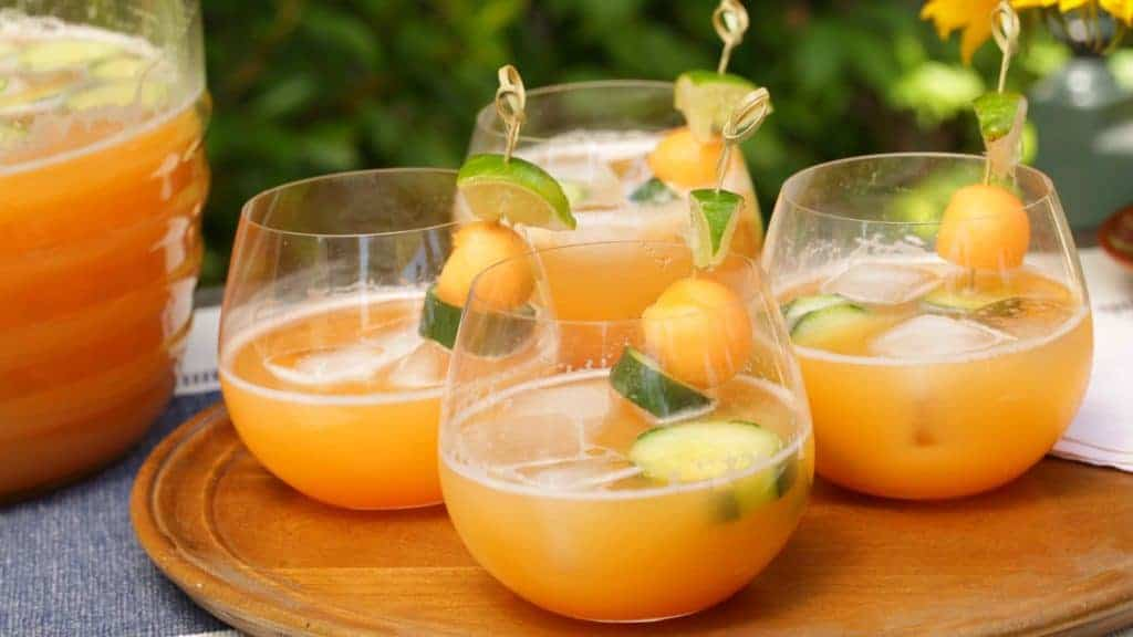 Glasses filled with canteloupe cucumber agua fresca garnished with melon balls and sliced cucumbers