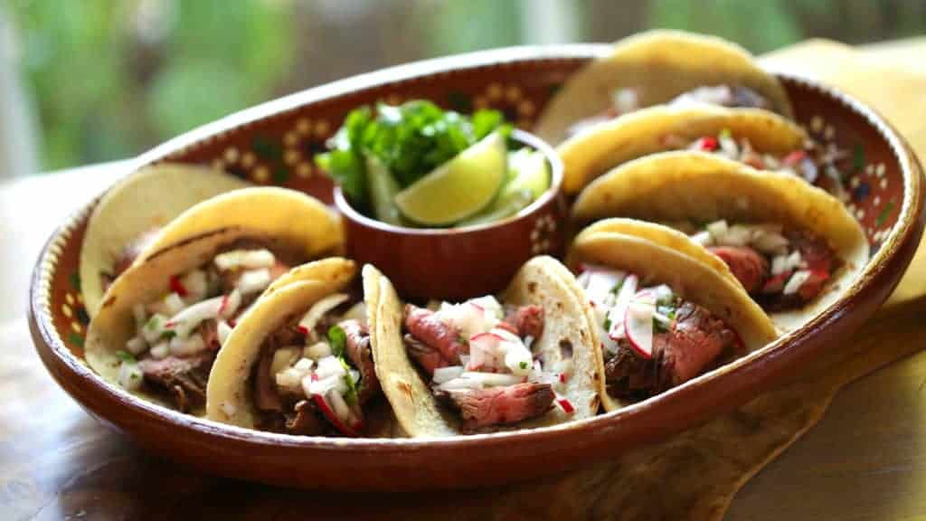 A terra-cotta platter filled with Carne Asada tacos