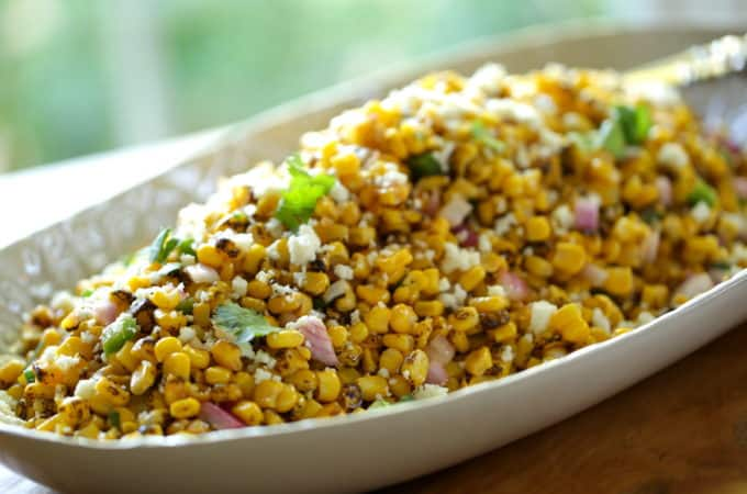 a platter filled with a charred Mexican corn salad