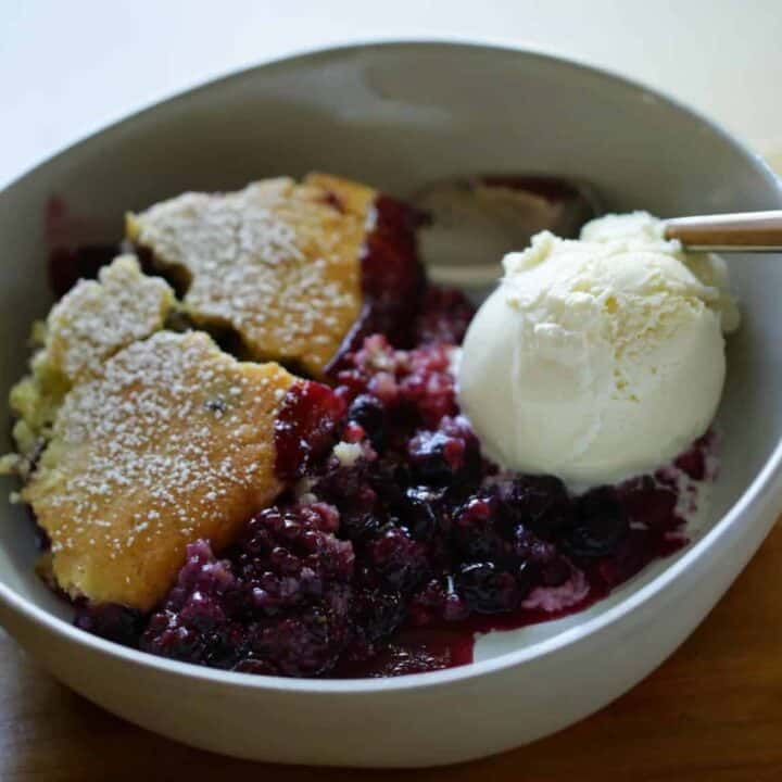 Triple Berry Campfire Cake Recipe in a white pottery bowl with a scoop of vanilla ice cream