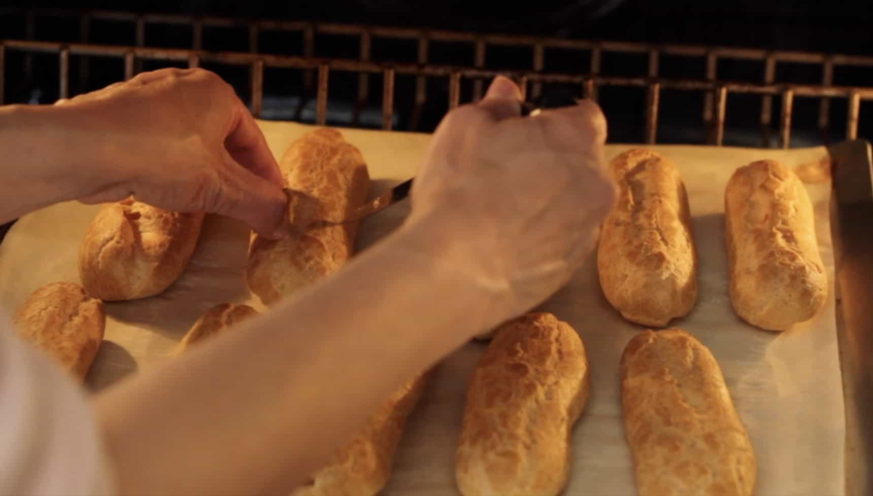 Creating a small incision in the eclair shell with a knife while in the oven to release steam