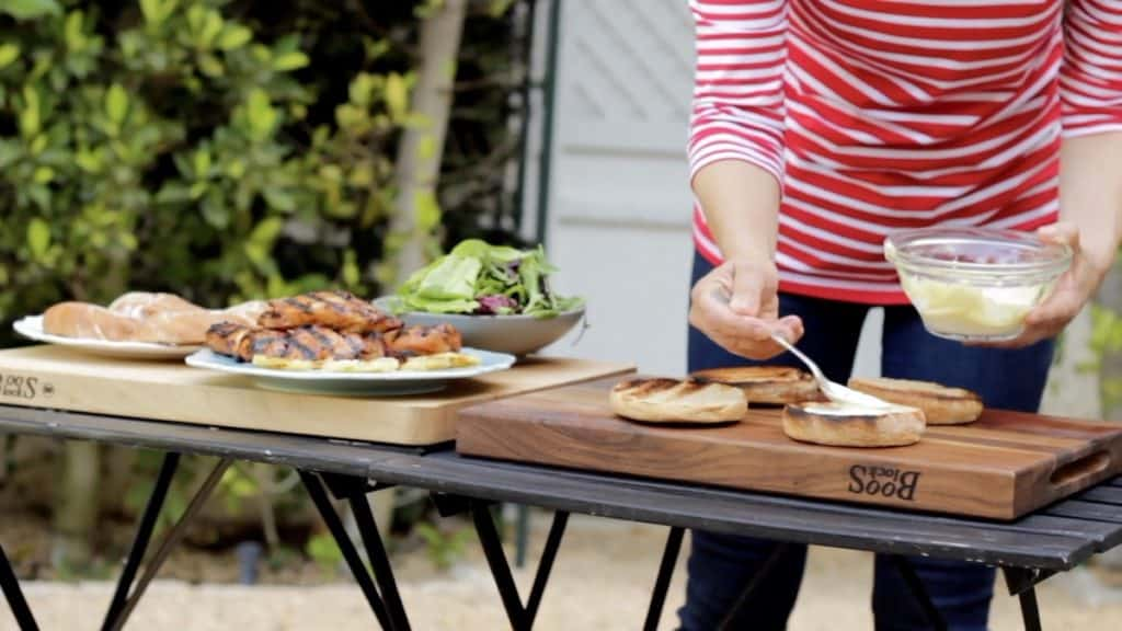 Assembling Grilled Chicken Sandwiches on outdoor tables