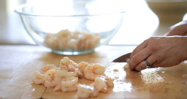 slicing cooked shrimp on a cutting board adding them to a bowl